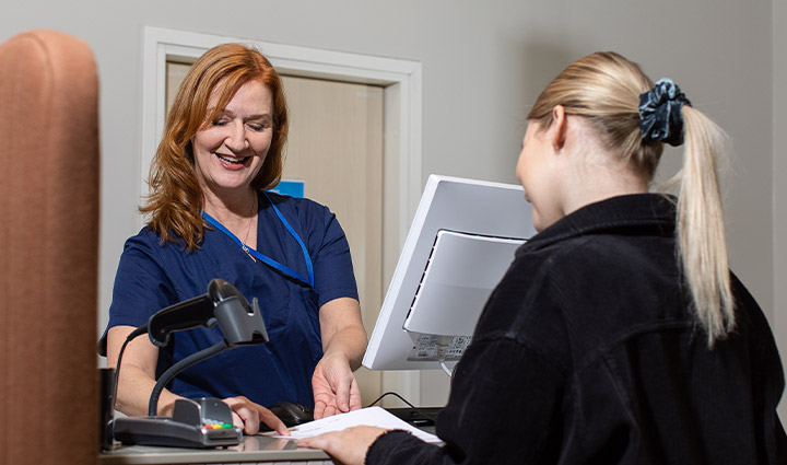 A smiling customer service person is pointing to a piece of paper to which a client is looking.