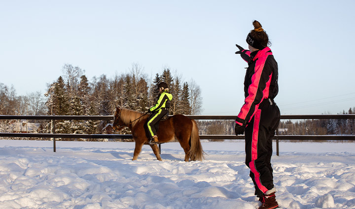 A client riding with a horse in a snowy enclosure. The riding instructor is giving instructions.