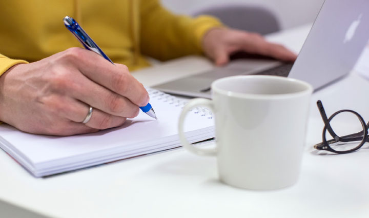 Kuvituskuva: kannettavan tietokoneen ääressä työskentelevä mies kirjoittaa muistiinpanoja vihkoon.