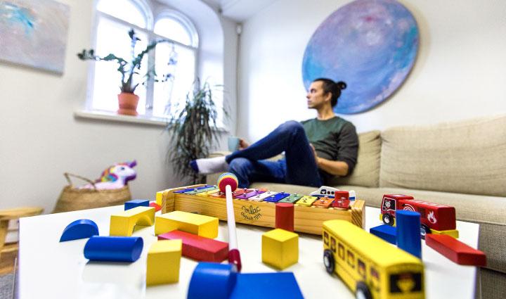 Kuvituskuva: sohvalla istuva mies katsoo ulos ikkunasta. Etualalla on pöydällä lasten leluja.